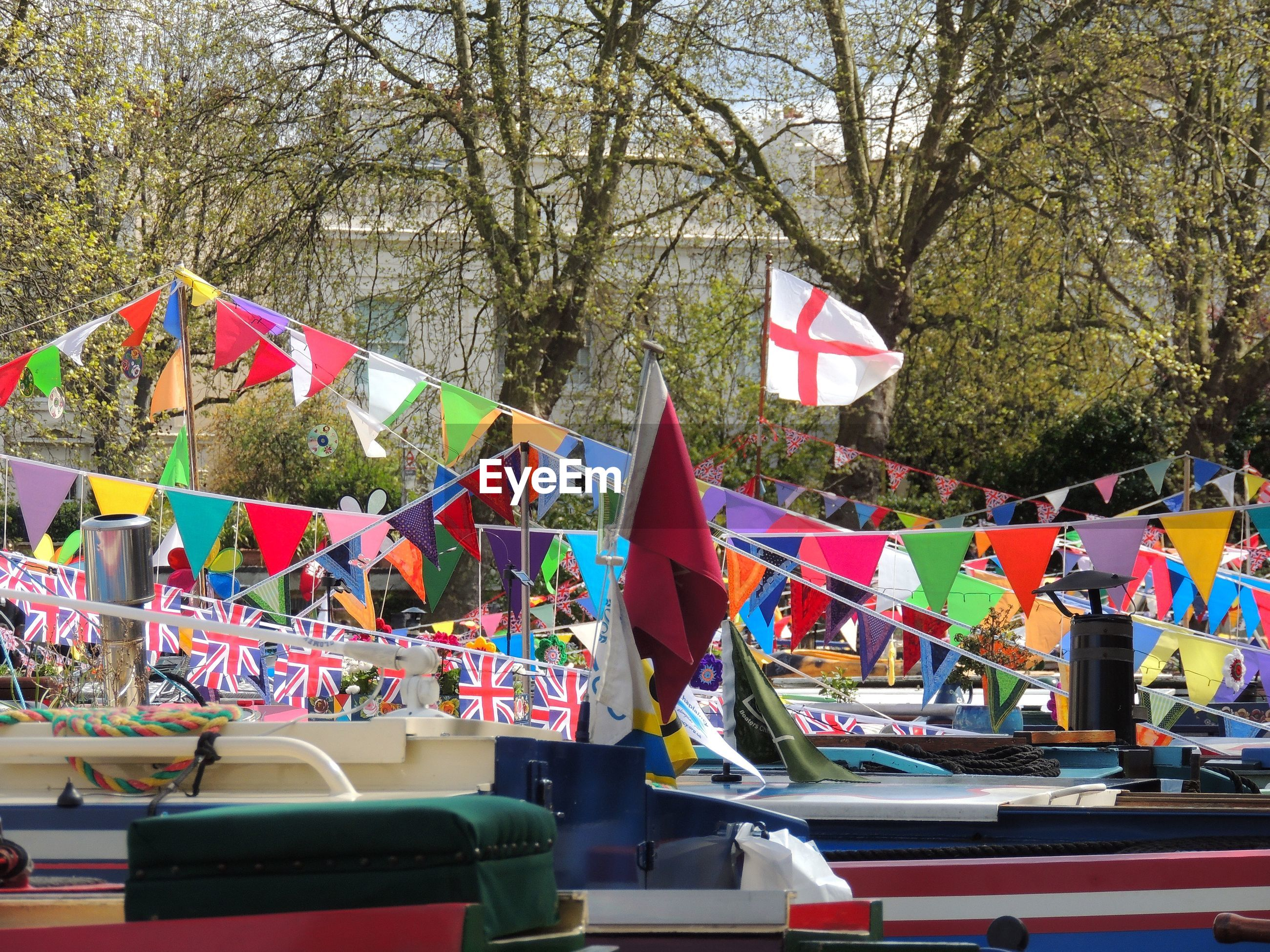Colorful buntings over boats against trees
