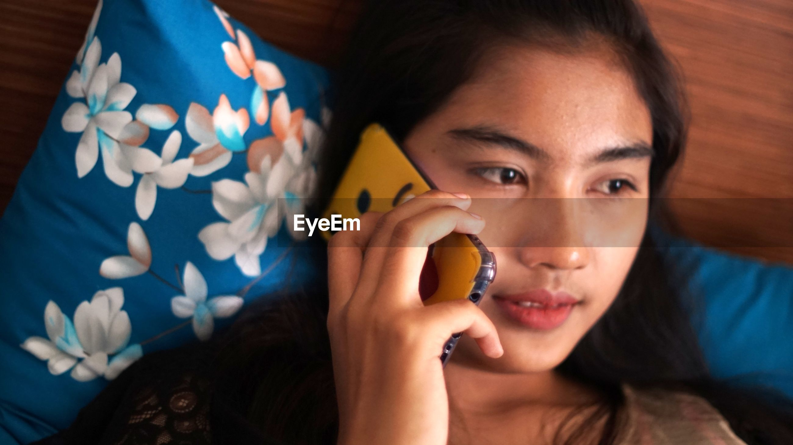 Close-up of young woman talking on phone while lying on bed at home