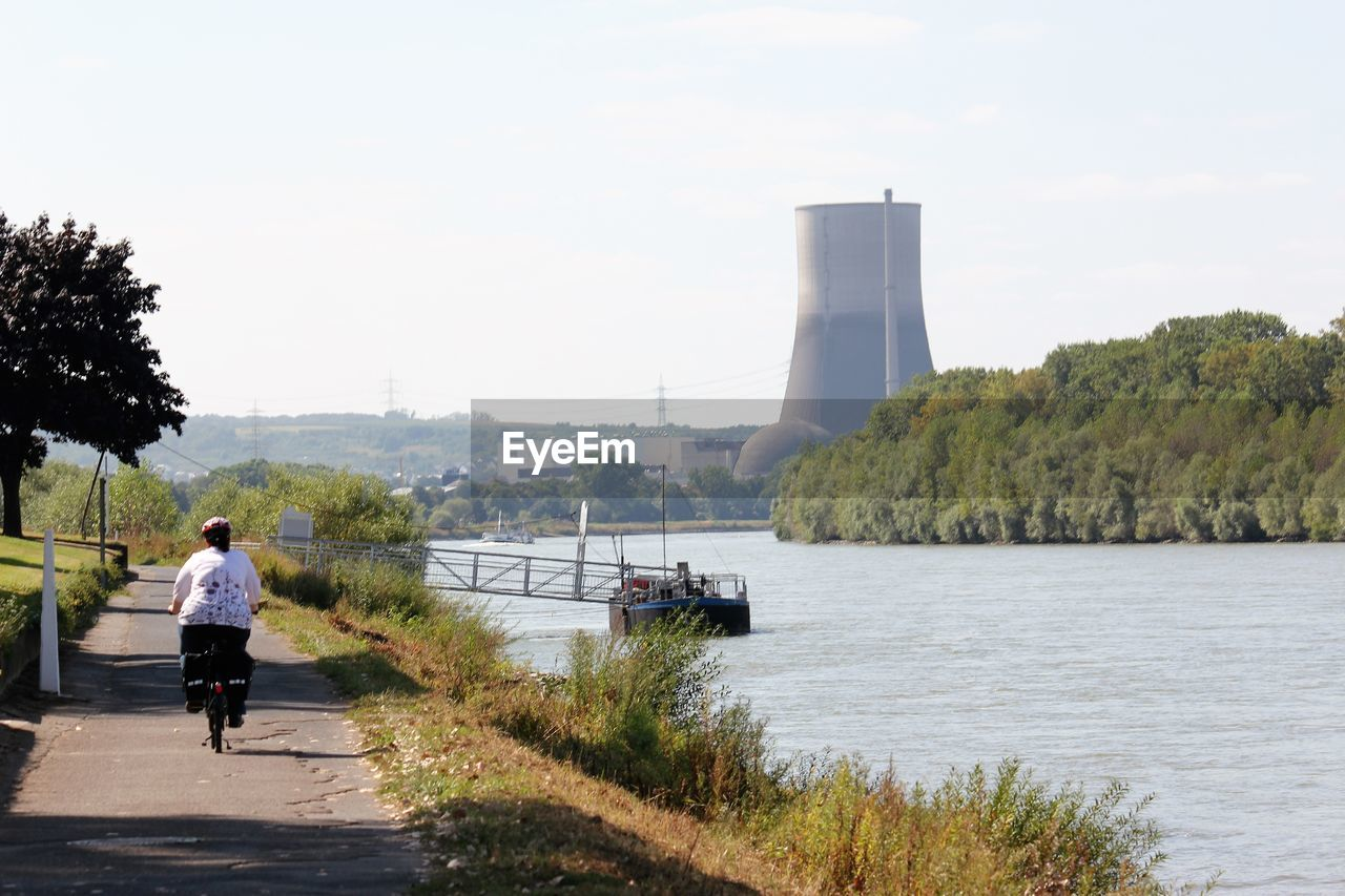 Woman cycling on riverbank against sky