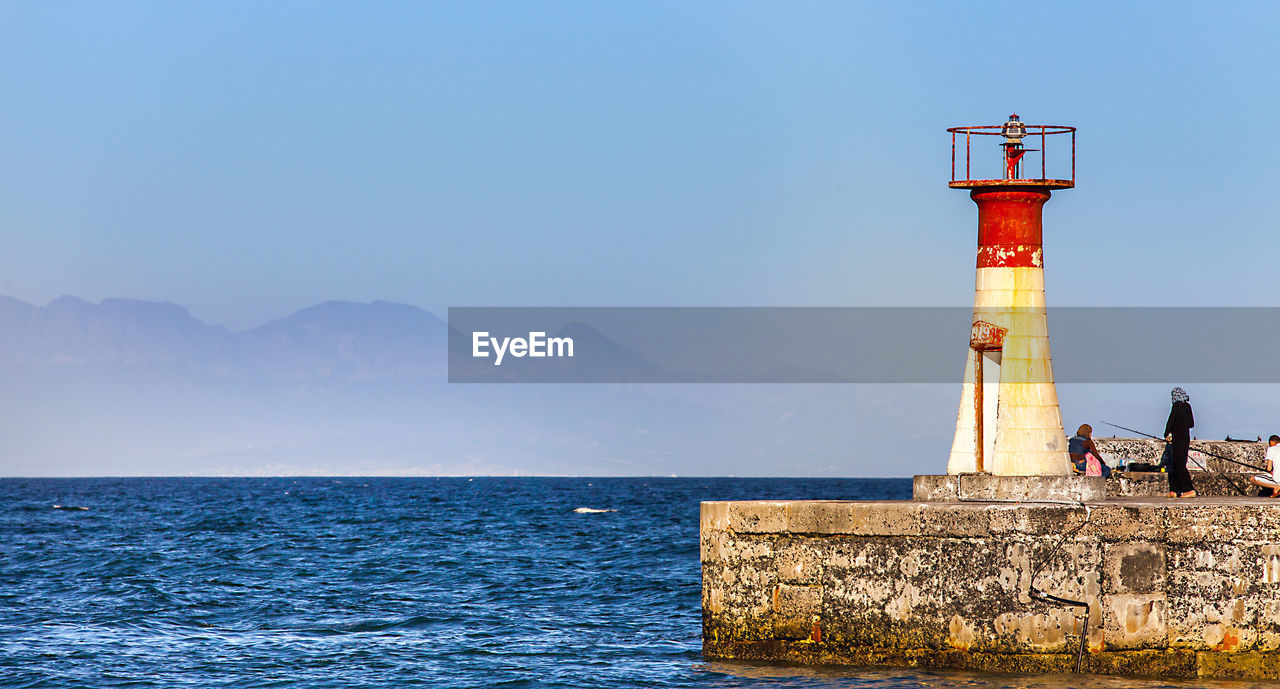 lighthouse, guidance, architecture, sea, safety, day, built structure, blue, clear sky, nature, outdoors, water, mountain, tranquility, scenics, beauty in nature, sky, building exterior, horizon over water, no people