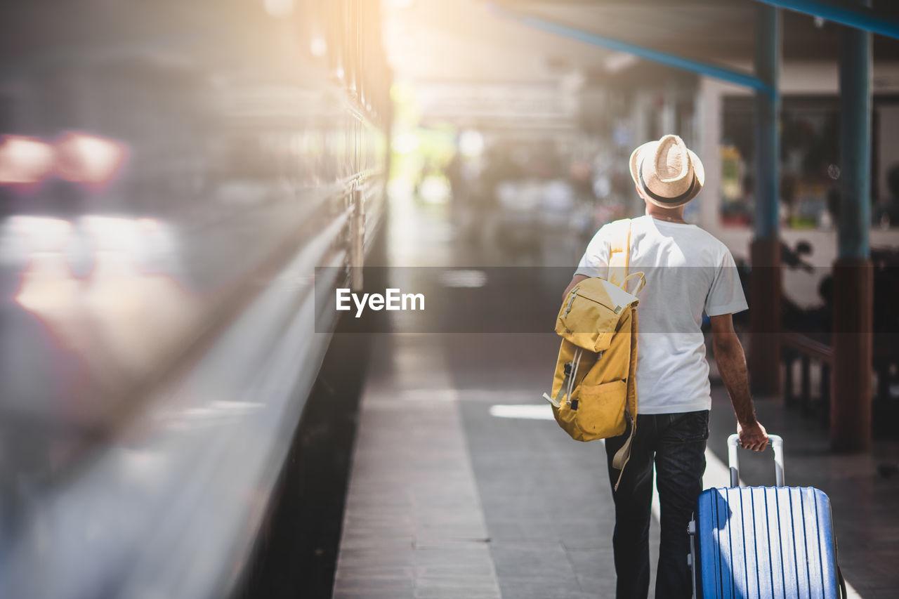 Rear view of man walking at railroad station platform