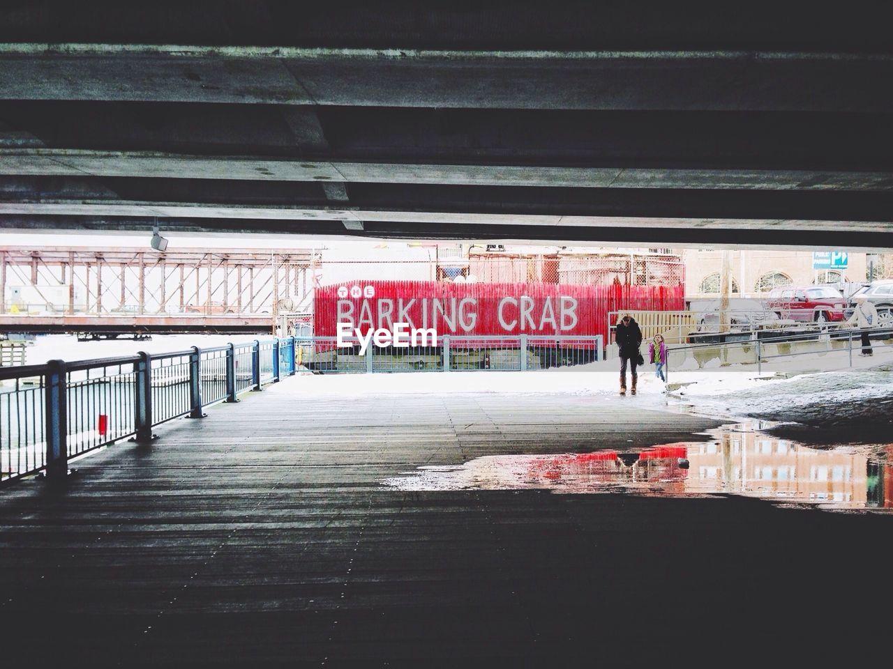 Man walking under bridge