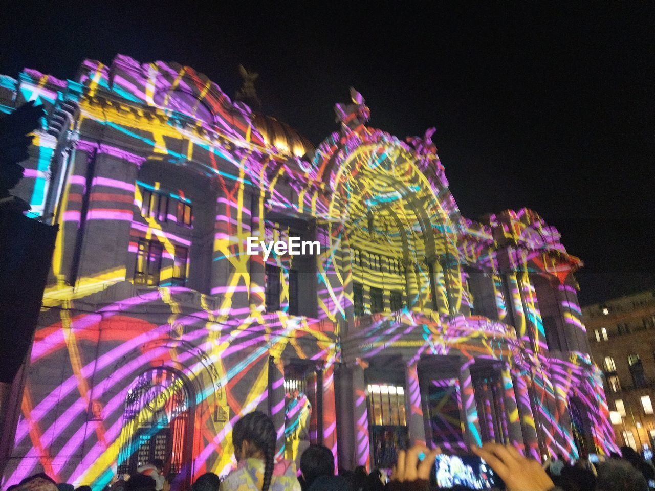 night, illuminated, low angle view, multi colored, celebration, building exterior, outdoors, amusement park, arts culture and entertainment, architecture, sky, built structure, large group of people, neon, city, people