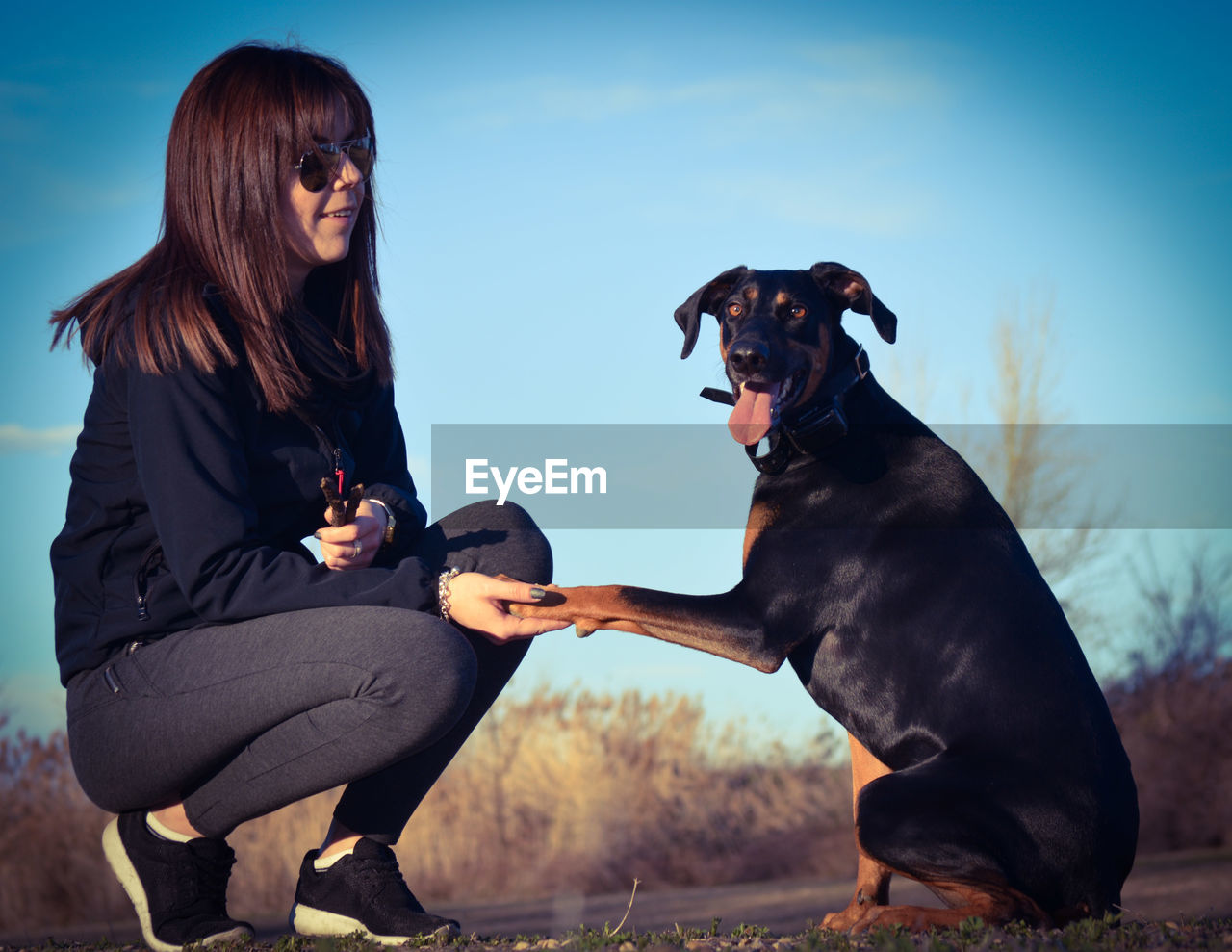 PORTRAIT OF WOMAN WITH DOG SITTING AGAINST SKY