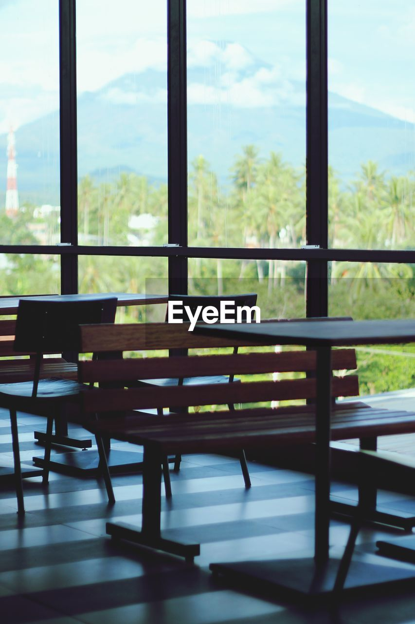 window, table, indoors, chair, no people, day, empty, furniture, tree, focus on foreground, nature, home interior, close-up