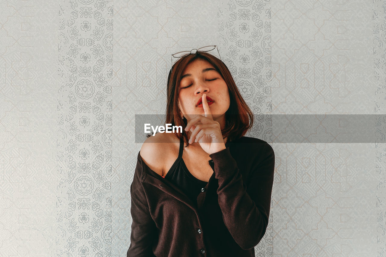 Woman with finger on lips standing by wall