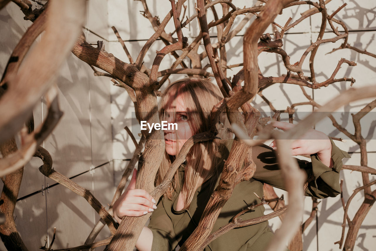 real people, portrait, one person, plant, headshot, branch, tree, selective focus, front view, leisure activity, lifestyles, close-up, young adult, looking, bare tree, day, nature, looking away, hairstyle