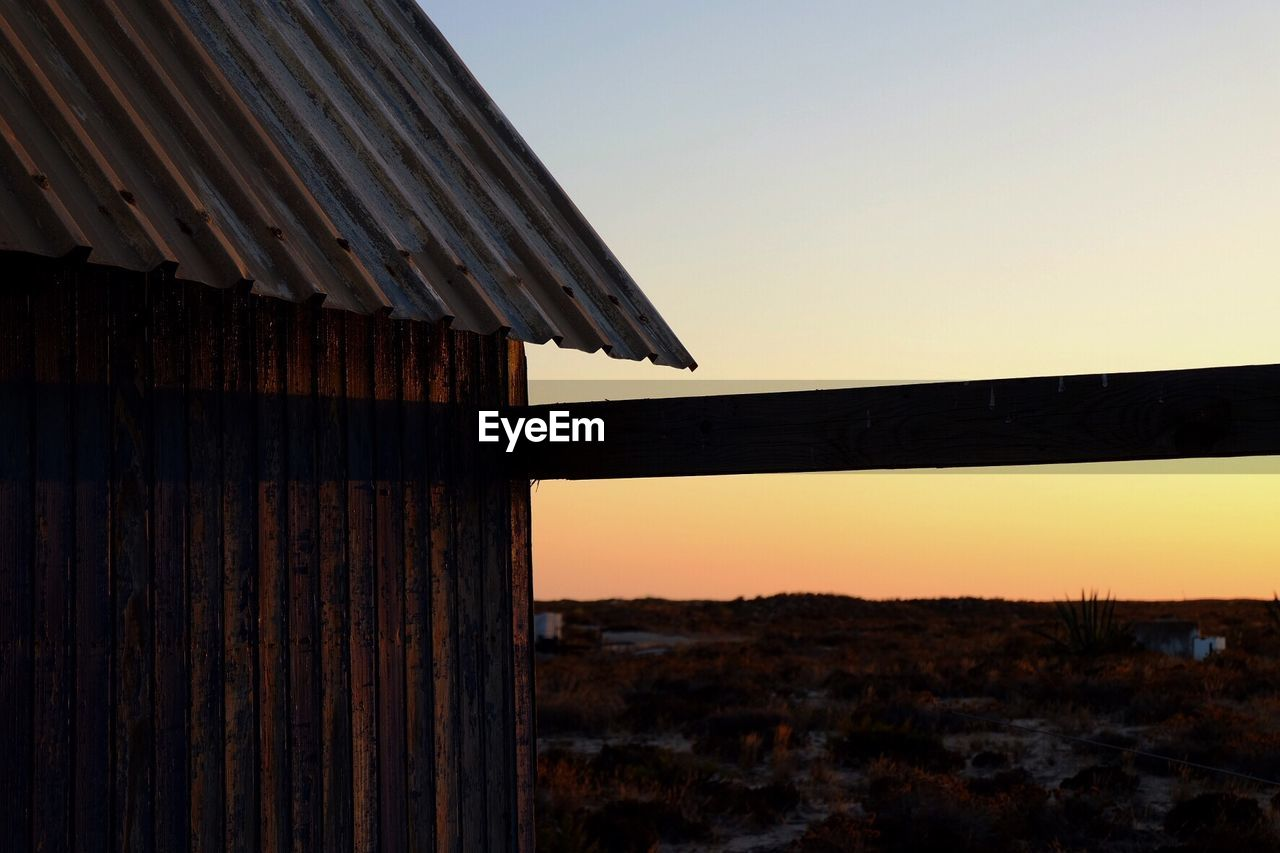 sky, sunset, architecture, built structure, nature, clear sky, no people, wood - material, roof, building exterior, copy space, outdoors, tranquility, orange color, land, environment, tranquil scene, old, landscape, scenics - nature