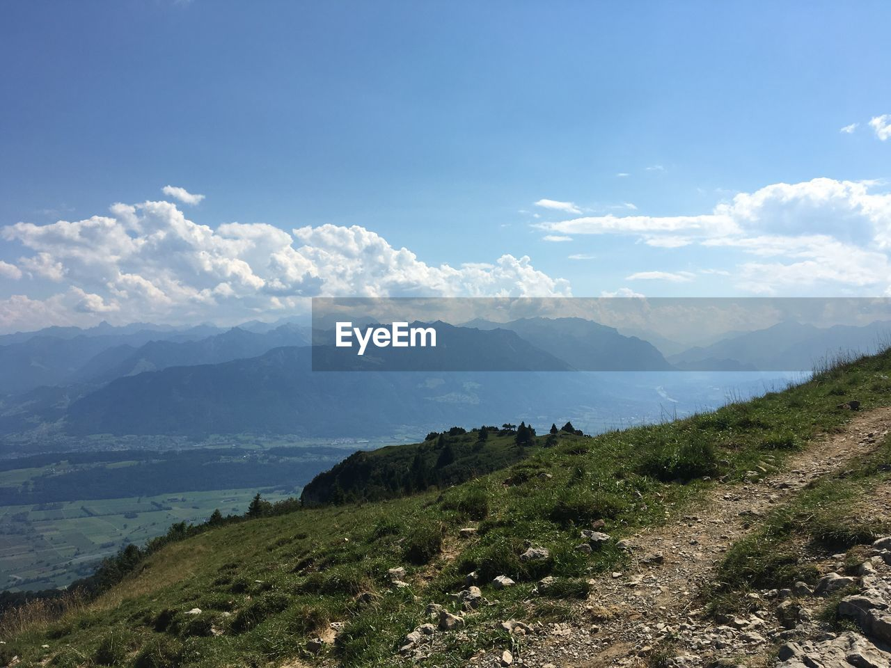 Panoramic Shot Of Countryside Landscape Against Mountain Range