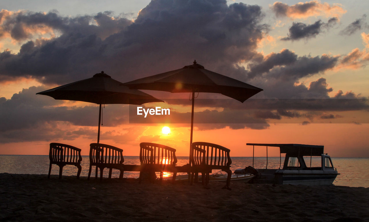 sunset, sky, sea, water, beach, land, cloud - sky, tranquility, orange color, scenics - nature, beauty in nature, nature, tranquil scene, silhouette, sand, horizon over water, horizon, chair, protection, outdoors, no people