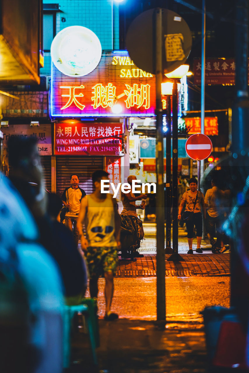 illuminated, night, city, street, architecture, city life, text, building exterior, built structure, group of people, communication, city street, lighting equipment, real people, sign, men, motion, people, store, leisure activity, neon, outdoors