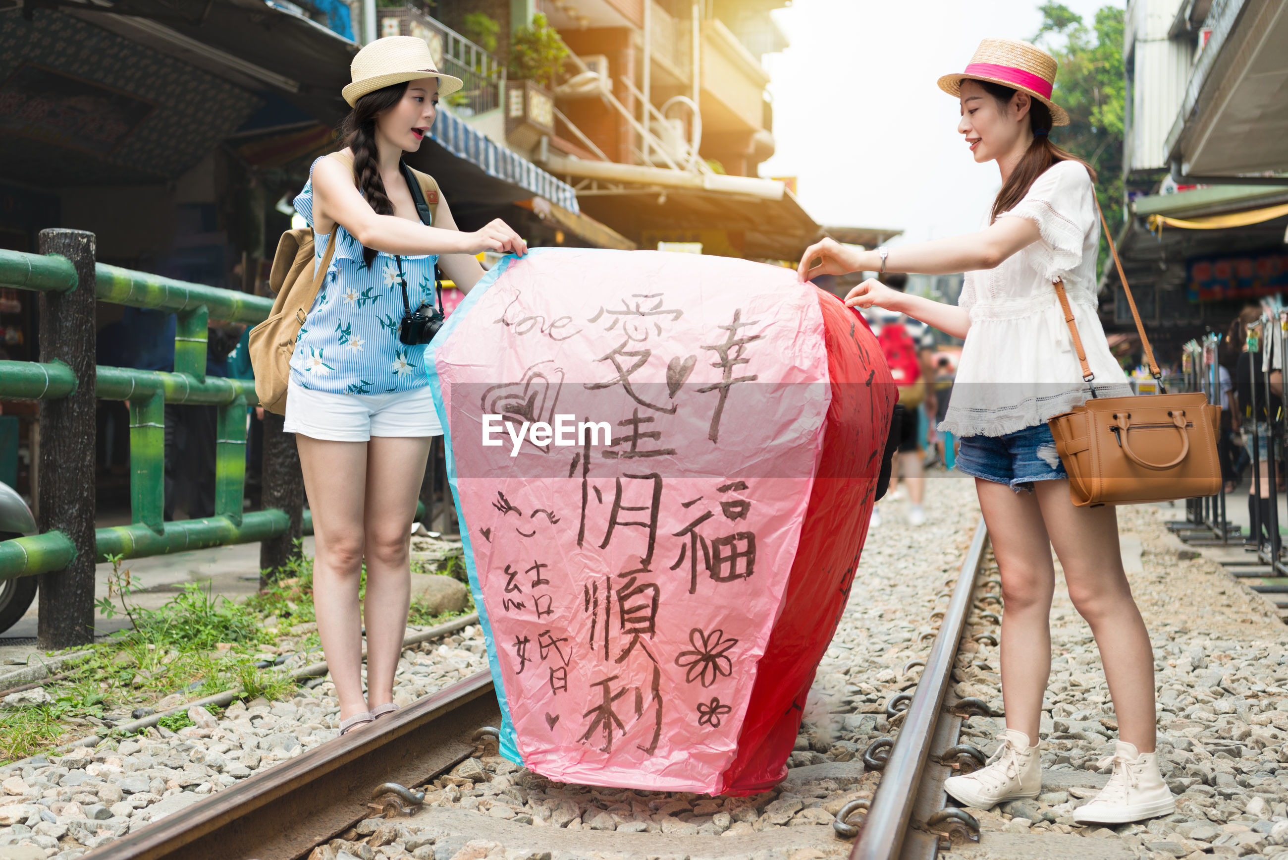 Women with paper lantern standing by railroad tracks