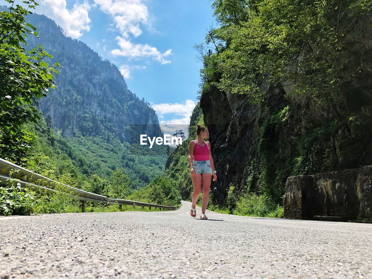 Woman walking on road amidst mountain against sky