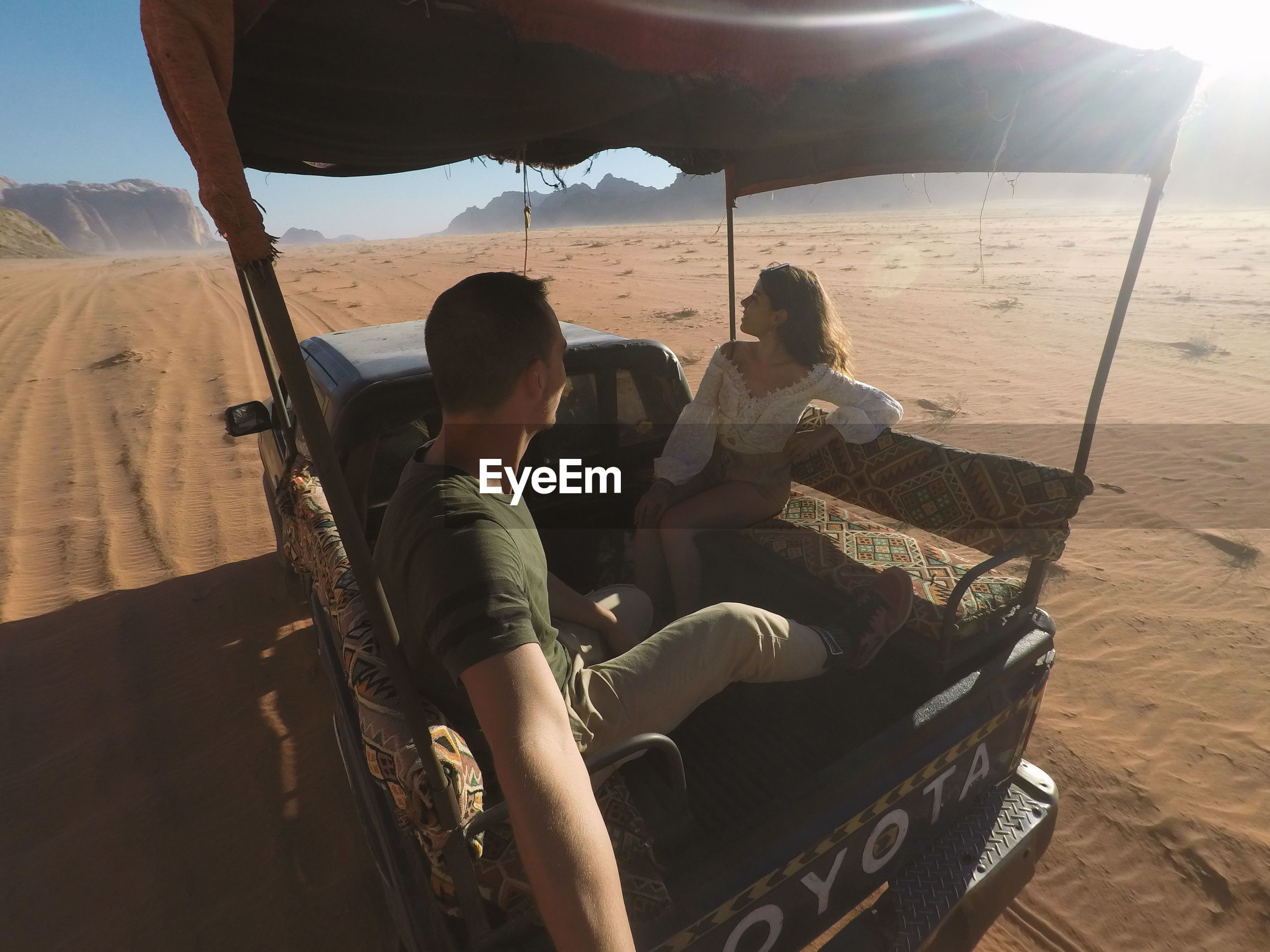 Couple sitting on the back of a car in the desert