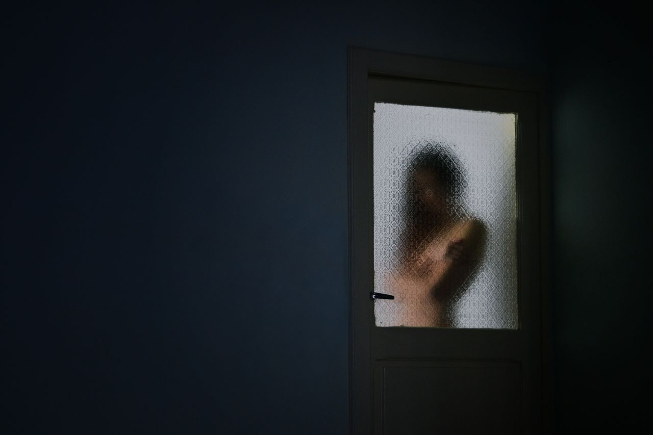 Woman Looking Through Frosted Window