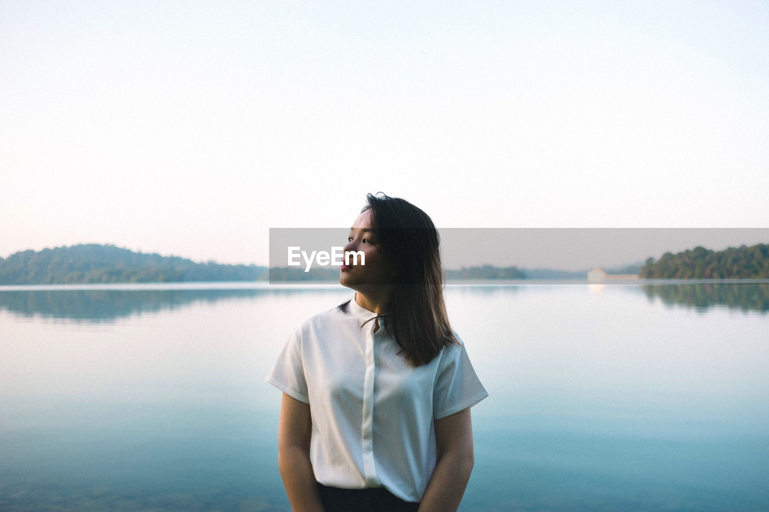 Young woman standing on lakeshore against sky