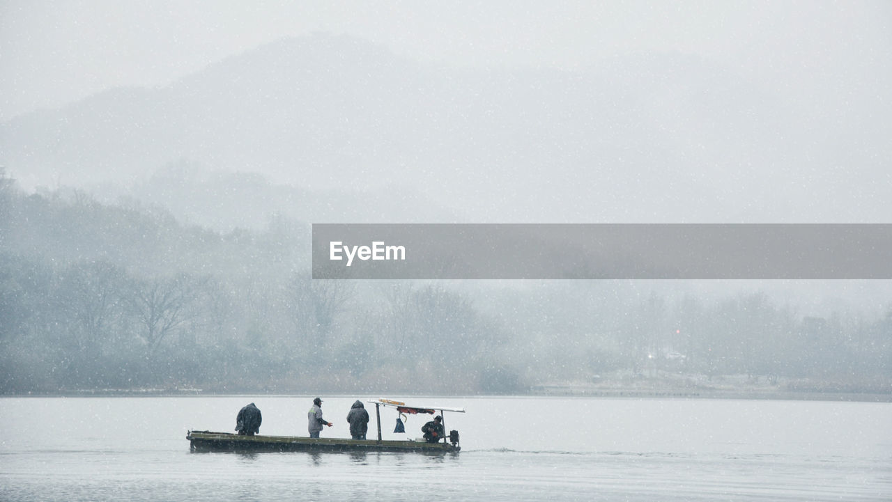 People In Snow On Lake Against Sky During Foggy Weather