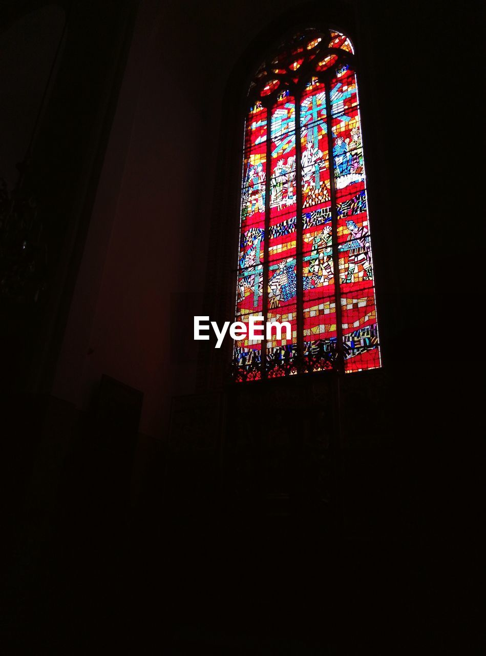 window, low angle view, religion, indoors, spirituality, place of worship, dark, no people, architecture, built structure, day