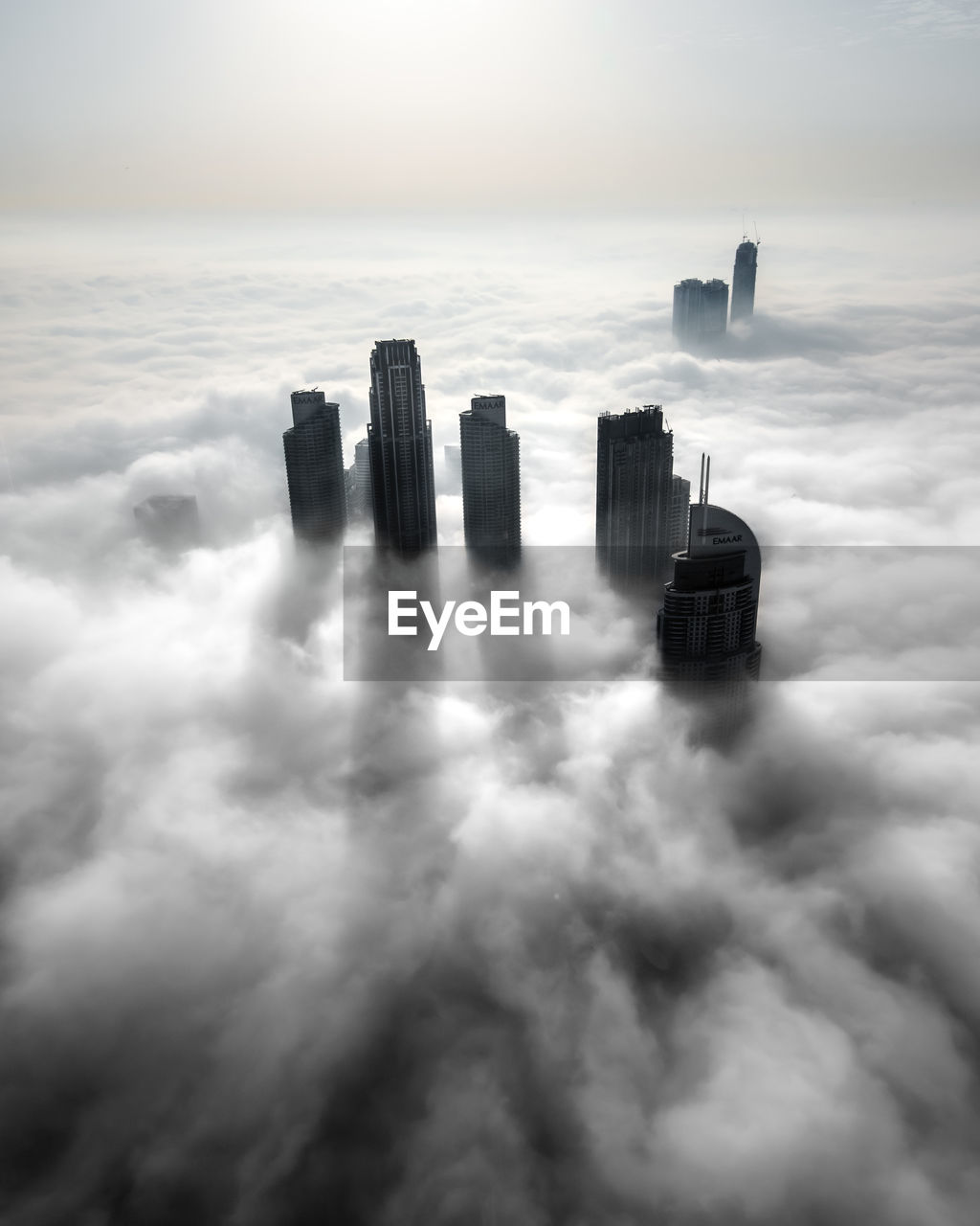 Aerial view of buildings against sky in city, covered by an early morning fog