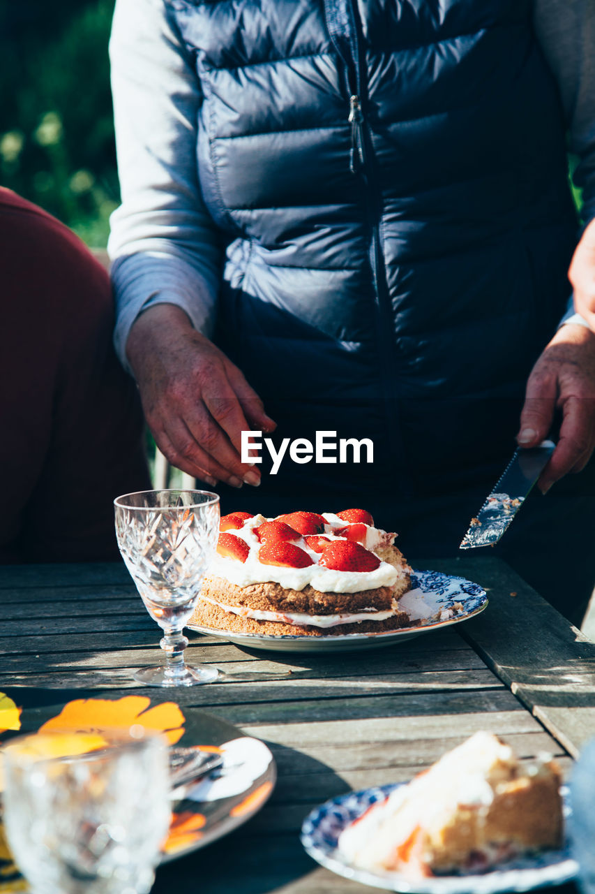 Midsection Of Woman Standing By Cake In Back Yard