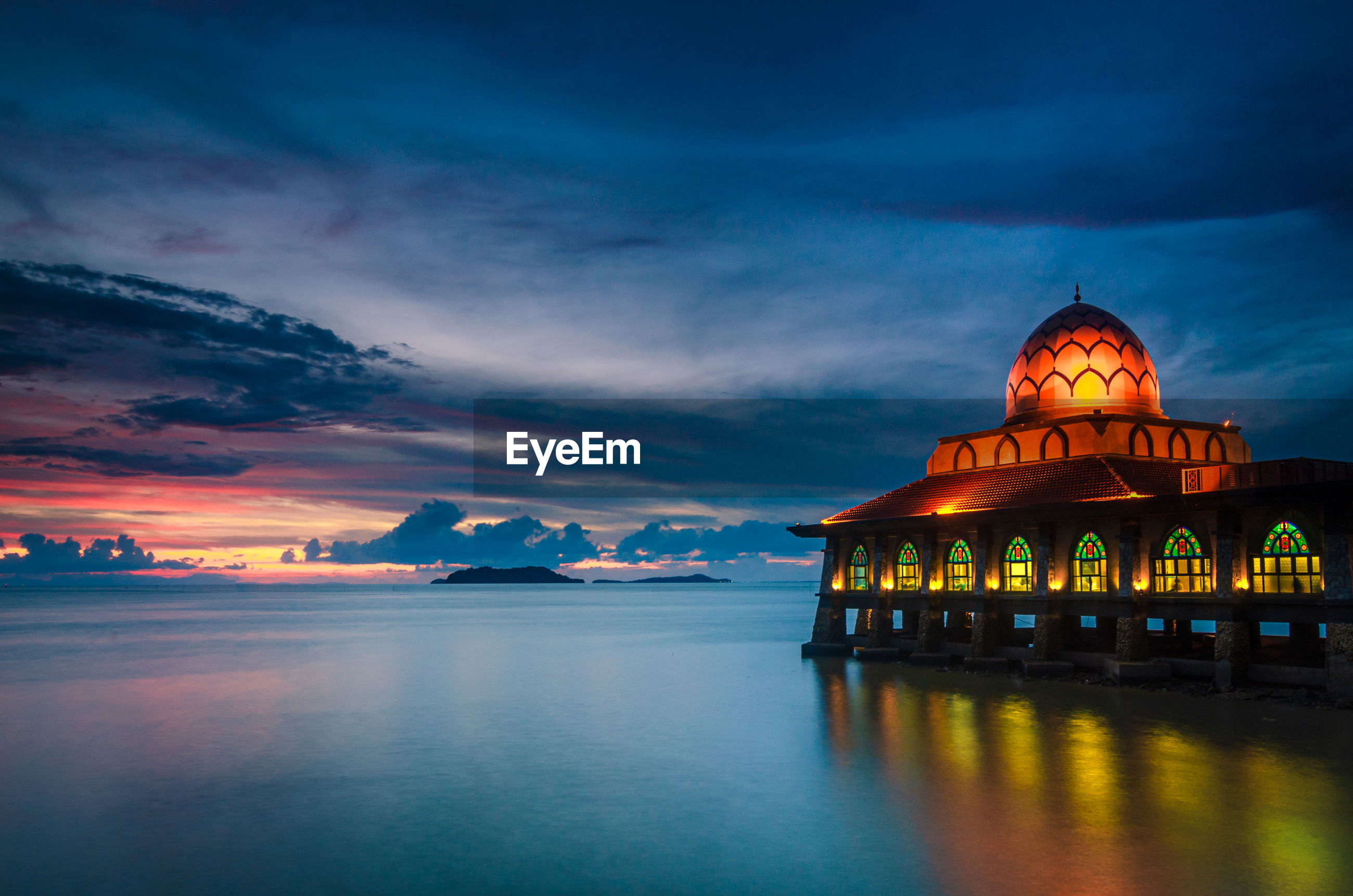 Illuminated mosque by sea at dusk