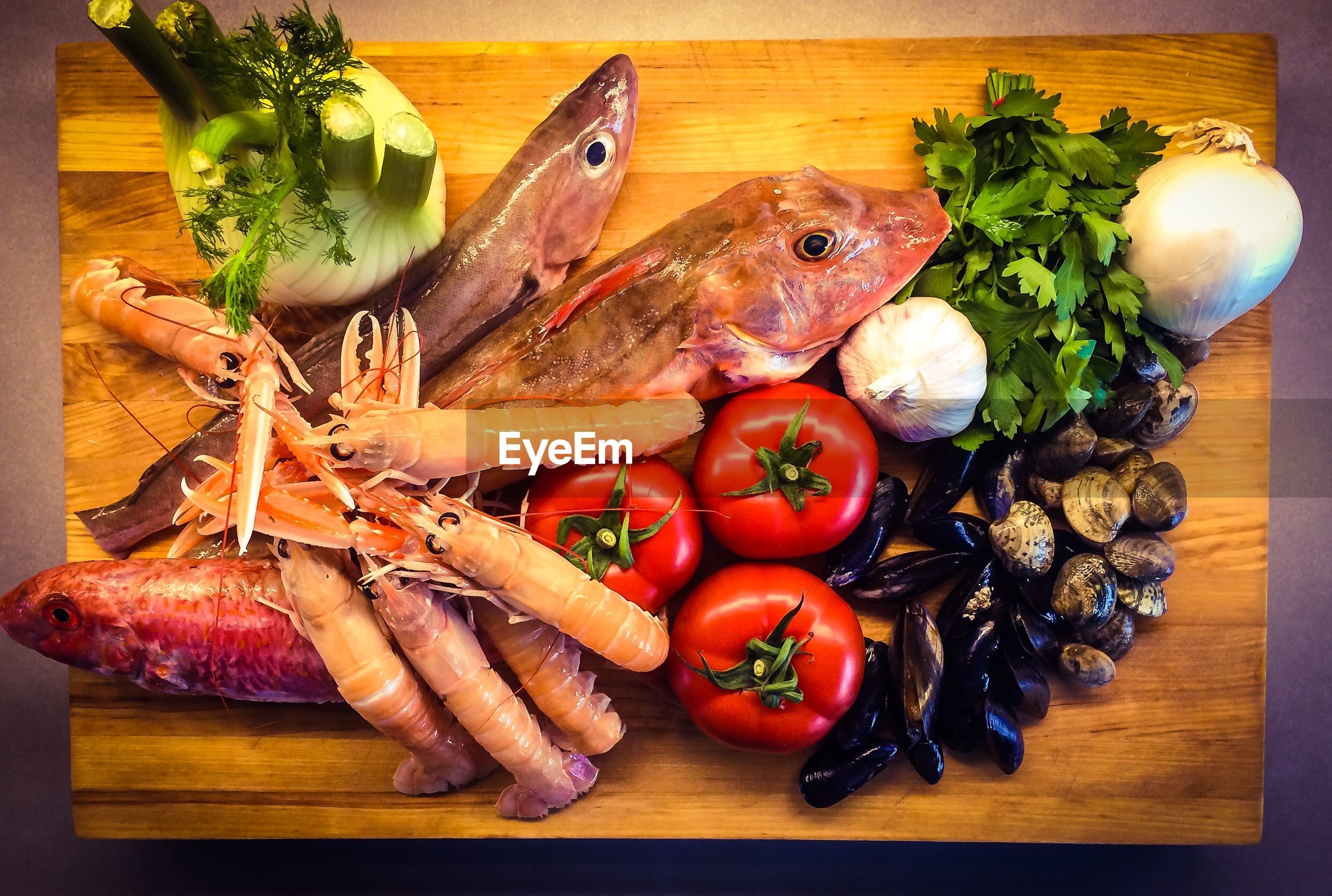 Directly above shot of seafoods with vegetables on cutting board