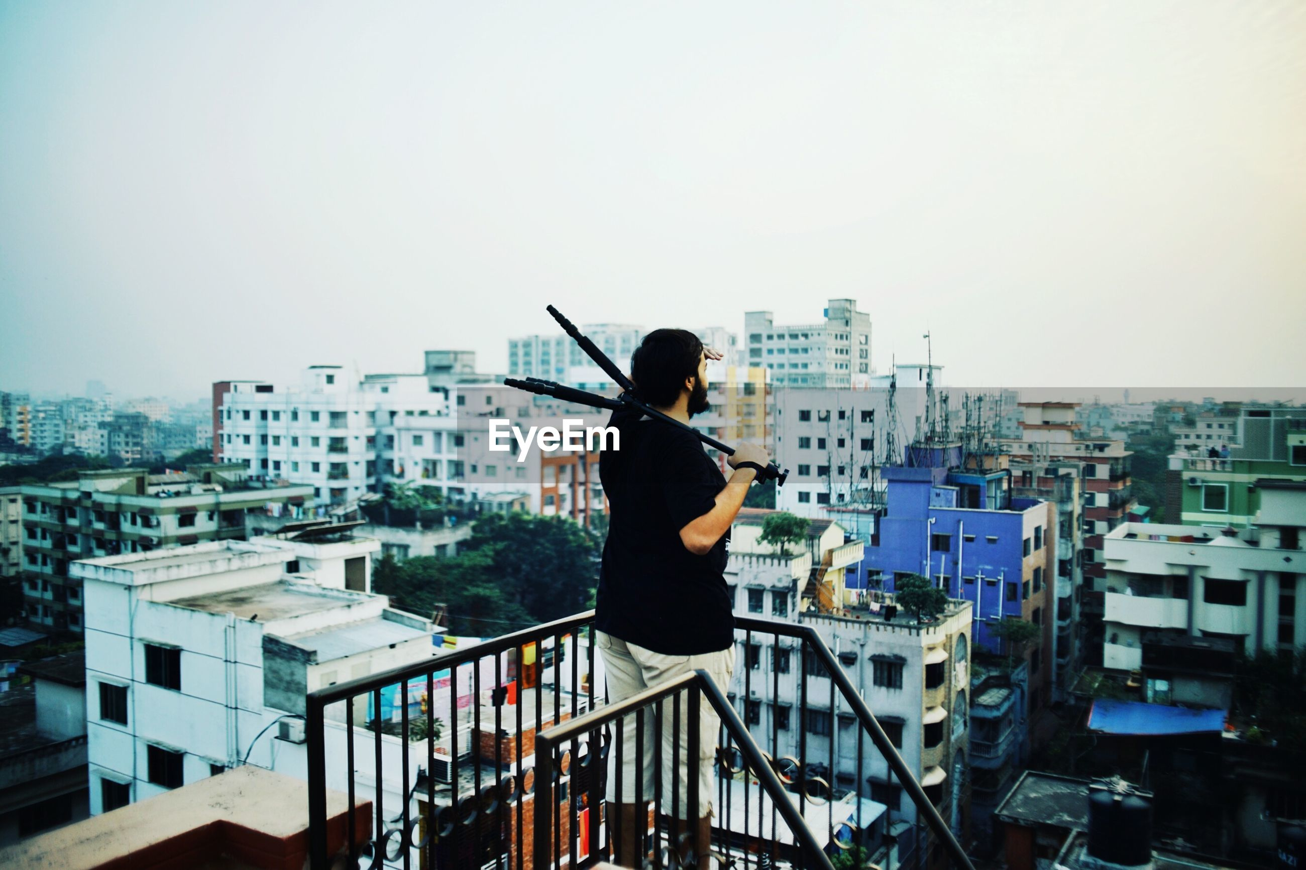 Side view of man holding tripod while standing on terrace in city