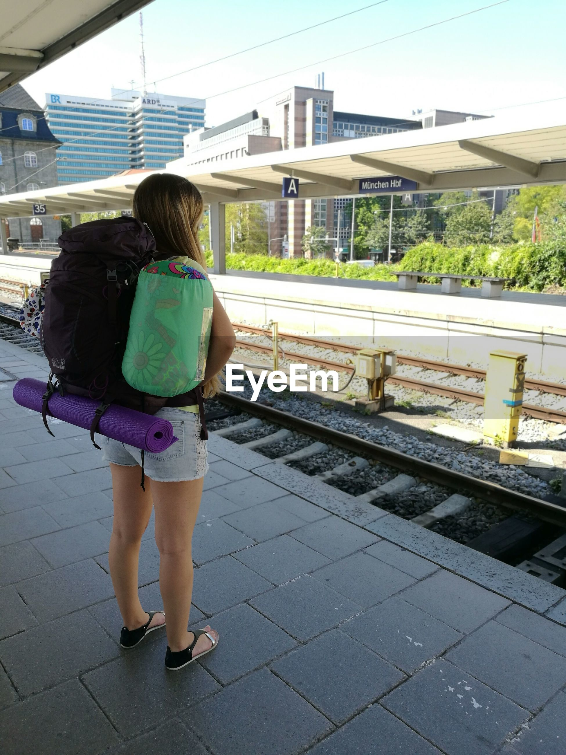 REAR VIEW OF WOMAN WALKING ON RAILROAD STATION PLATFORM