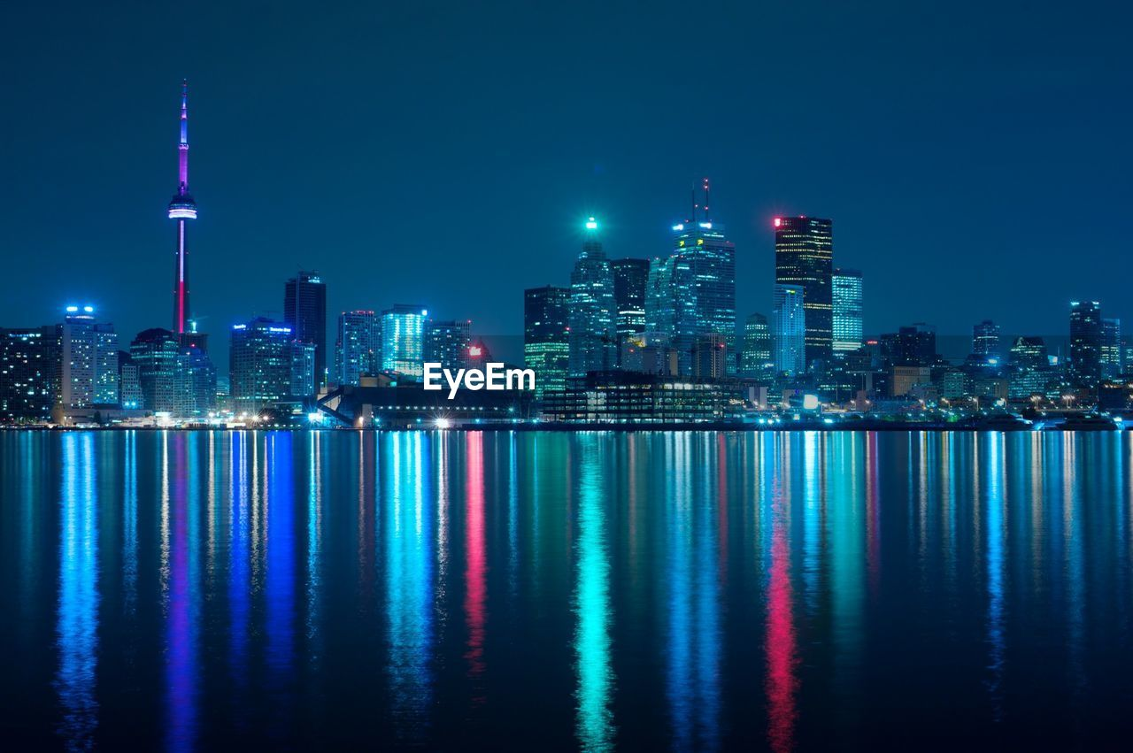 Illuminated skyscrapers by lake ontario against sky