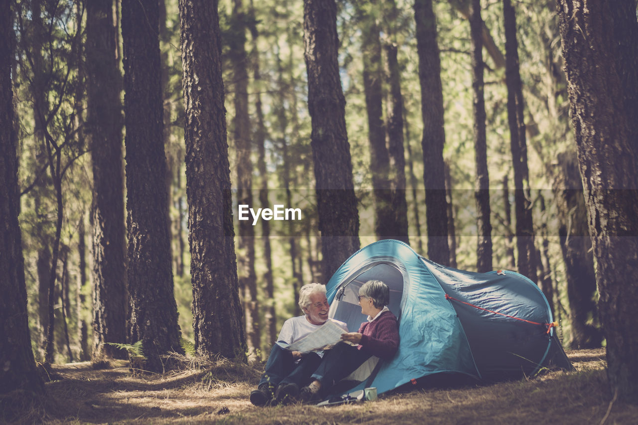 Couple Reading Map While Sitting By Tent Against Trees