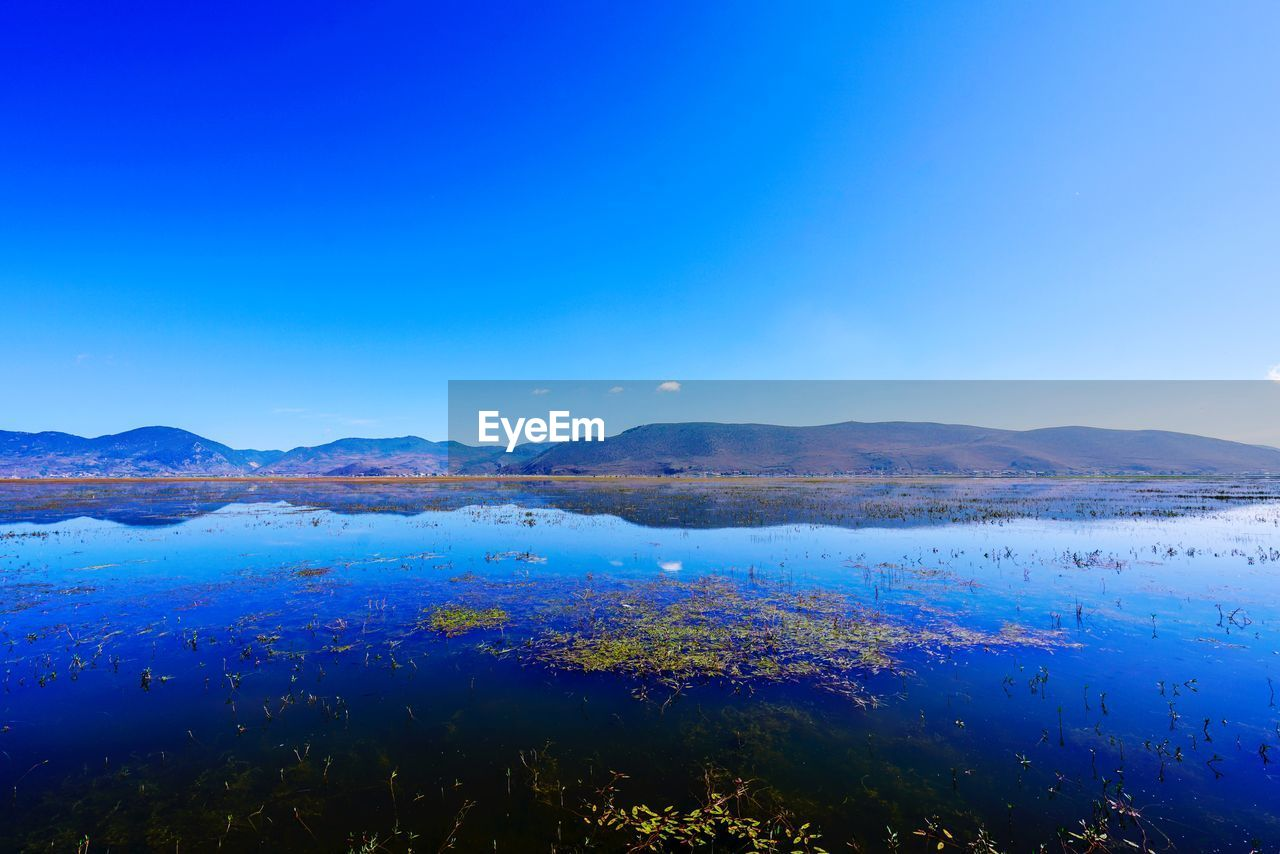 tranquility, tranquil scene, scenics, beauty in nature, blue, water, nature, lake, no people, outdoors, mountain, remote, day, clear sky, mountain range, landscape, sky