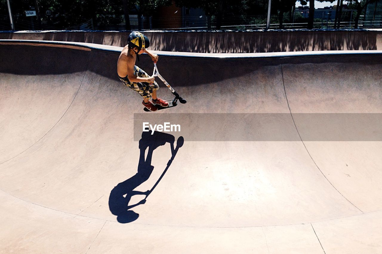 High Angle View Of Boy With Push Scooter Performing Stunt At Skateboard Park