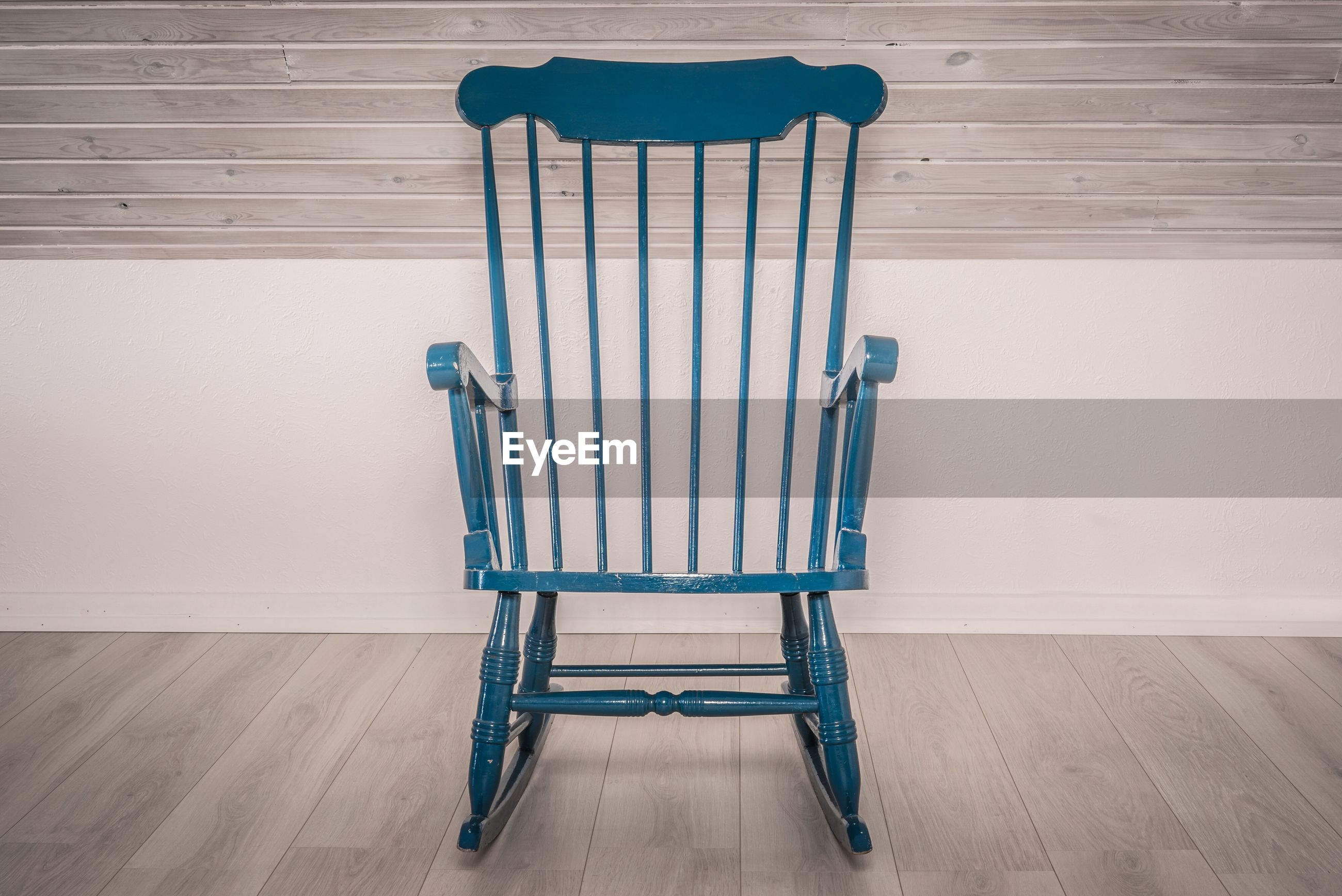 Empty chair against wall on hardwood floor at home