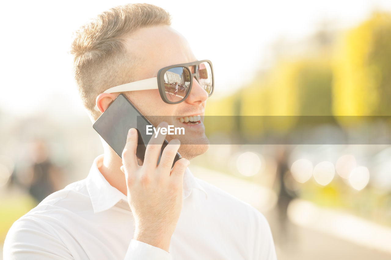 Close-Up Of Businessman Talking On Phone In City