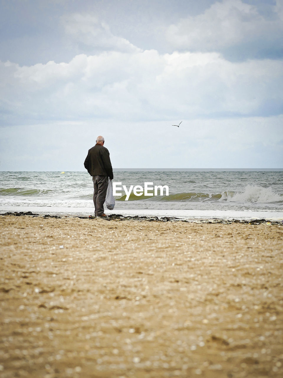 sea, beach, land, water, one person, sky, cloud - sky, real people, horizon, beauty in nature, men, lifestyles, leisure activity, horizon over water, scenics - nature, standing, day, full length, outdoors