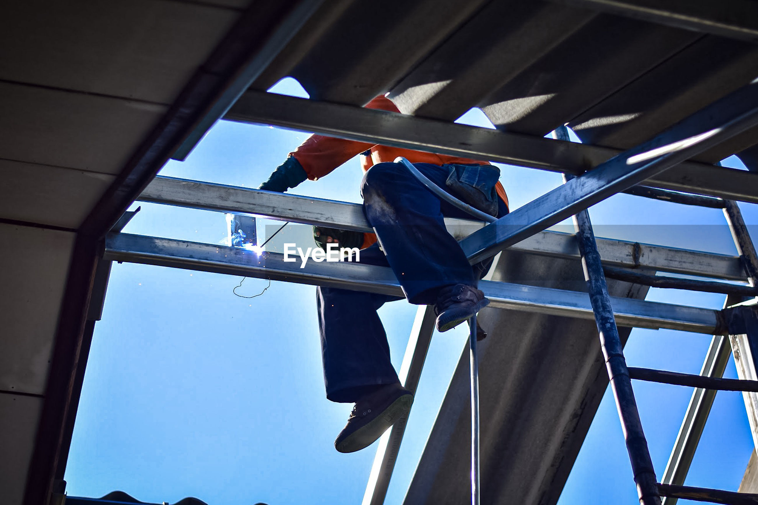 Low angle view of construction worker welding roof beam against blue sky