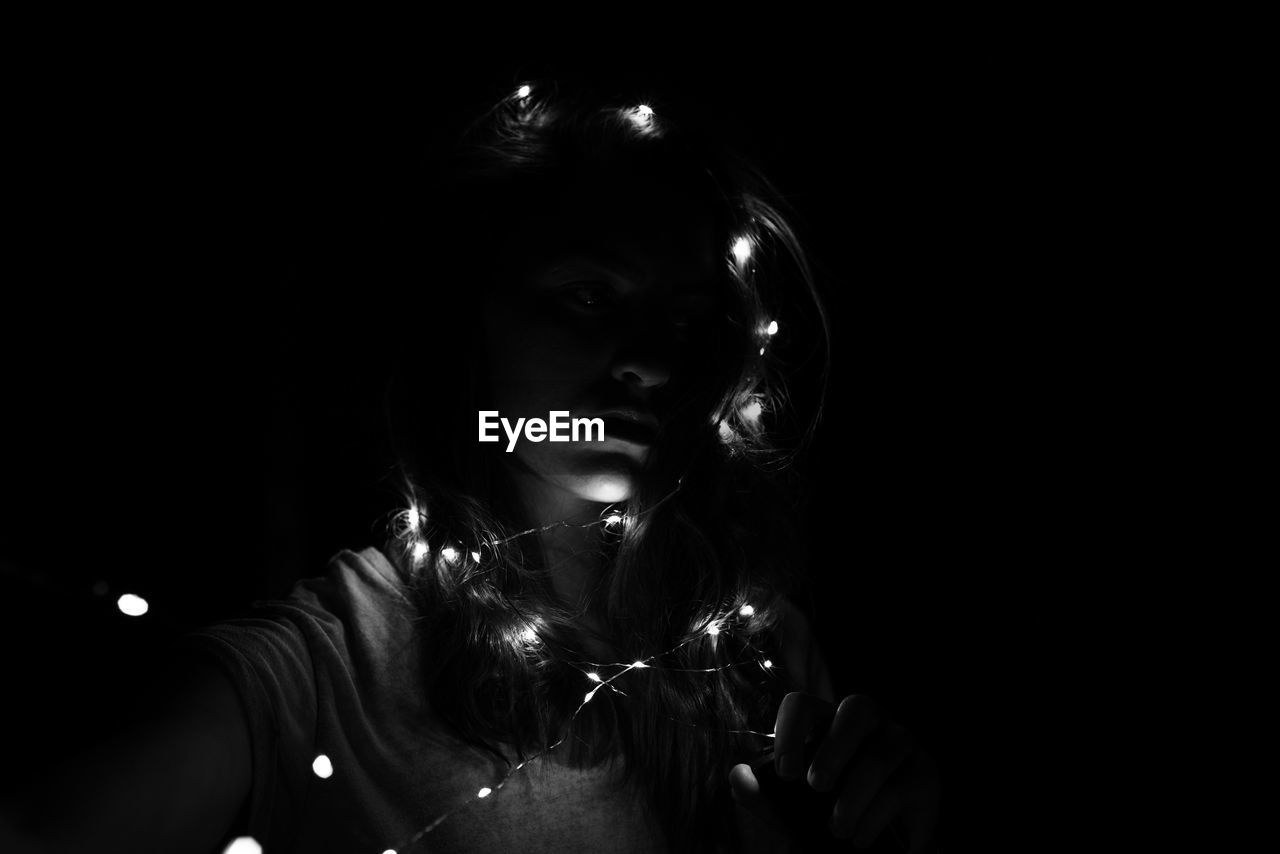 Girl with illuminated string lights against black background