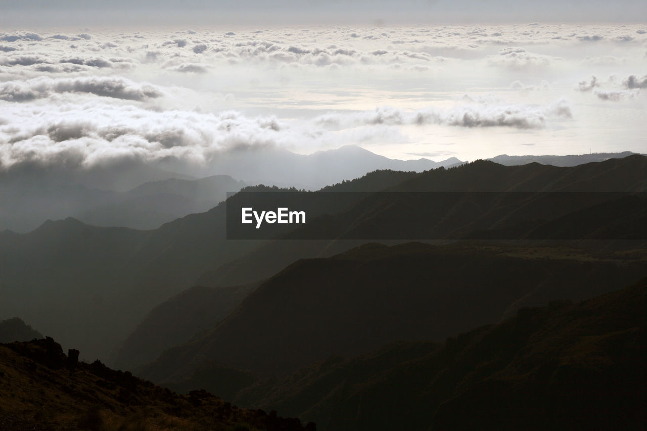 Morning mountain scenery with gradient grey color peaks and low clouds. sunrise. portugal, madeira