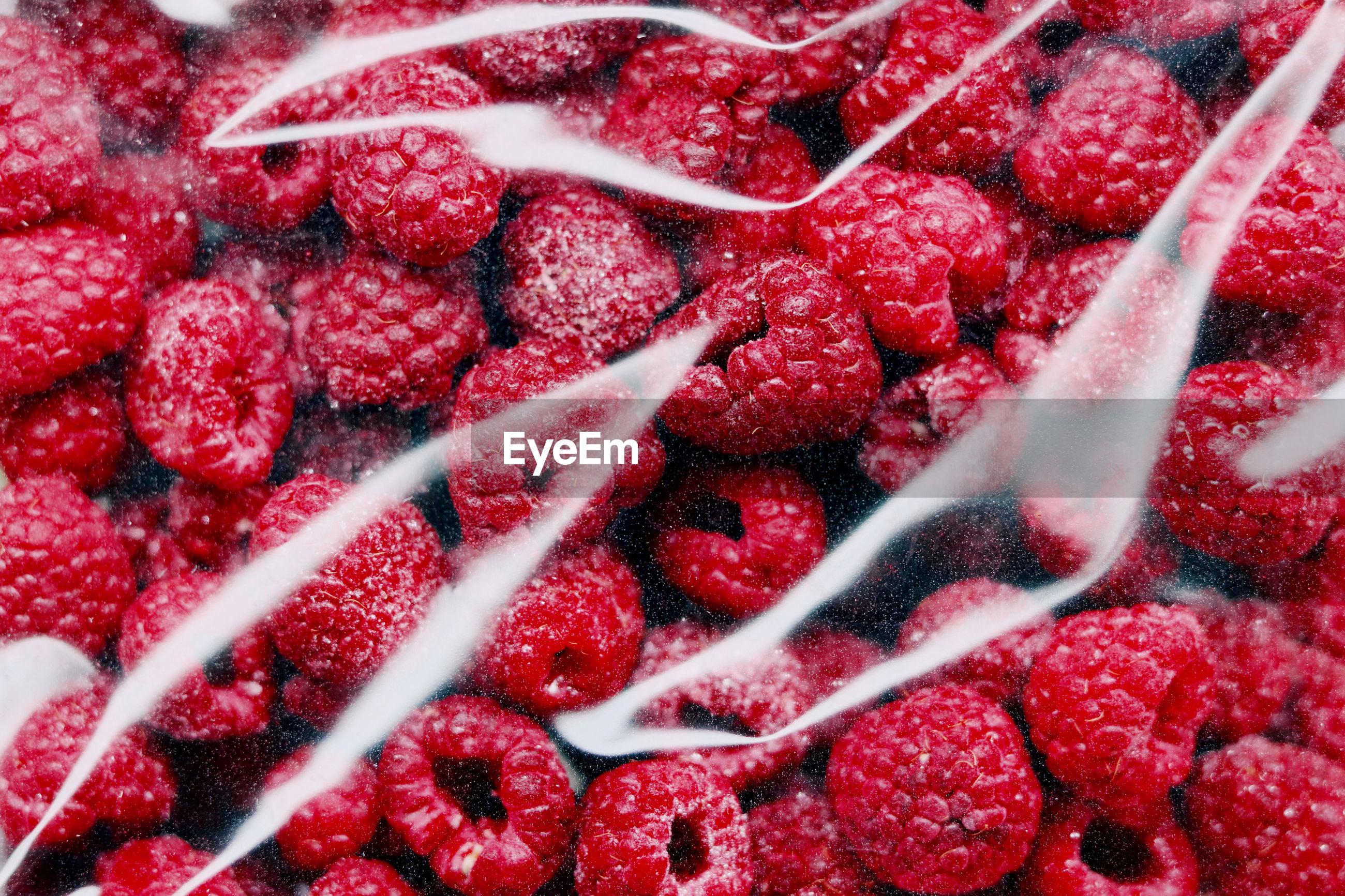 Full frame shot of raspberries in plastic