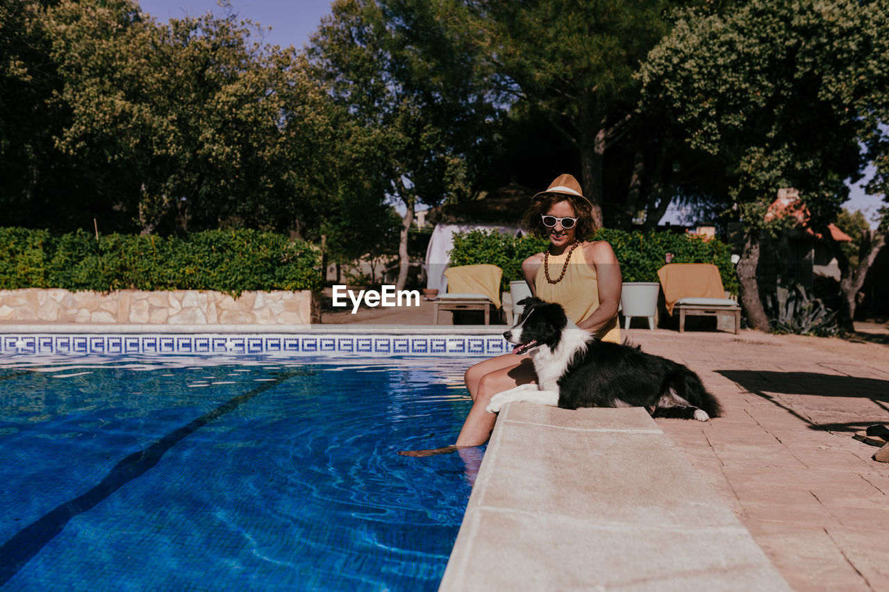 WOMAN WITH DOG AT SWIMMING POOL
