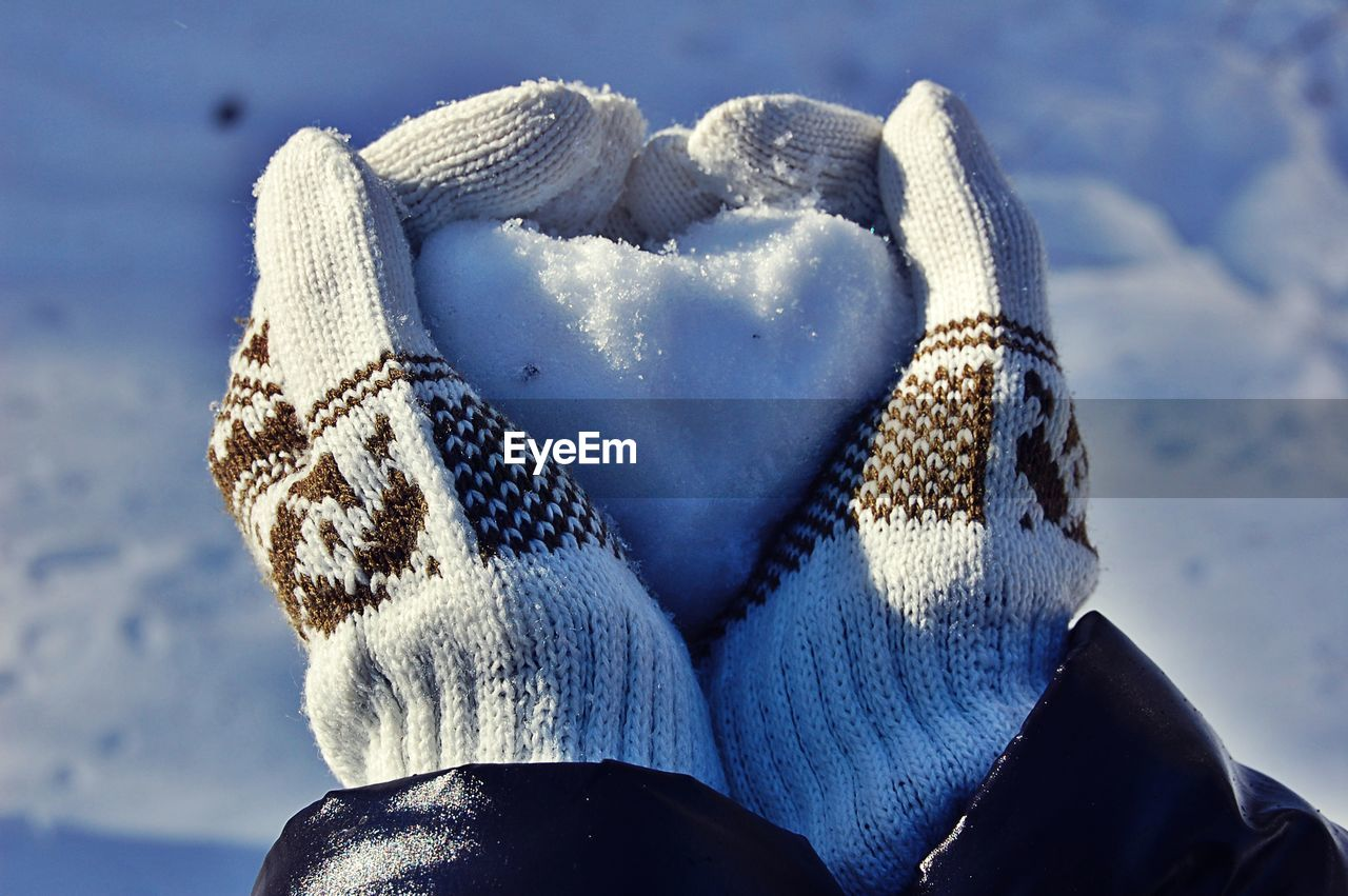 Hand holding snow of heart shape