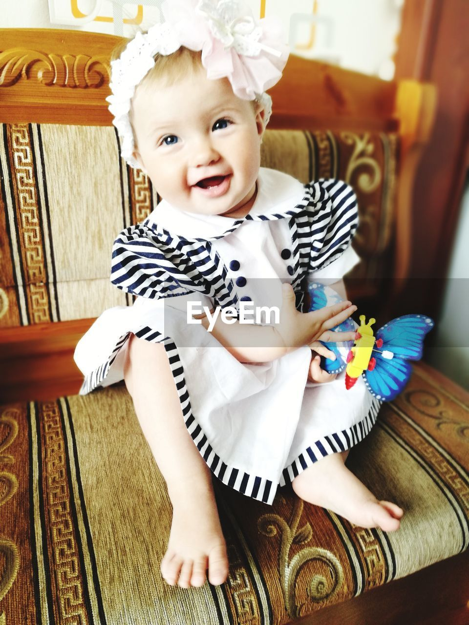 real people, one person, baby, indoors, home interior, innocence, childhood, cute, looking at camera, front view, sitting, portrait, babyhood, full length, day, playing, lifestyles, bed