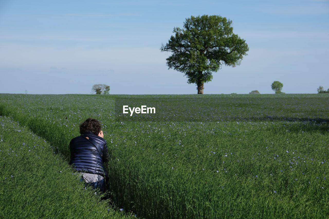 REAR VIEW OF MAN ON GRASSY FIELD