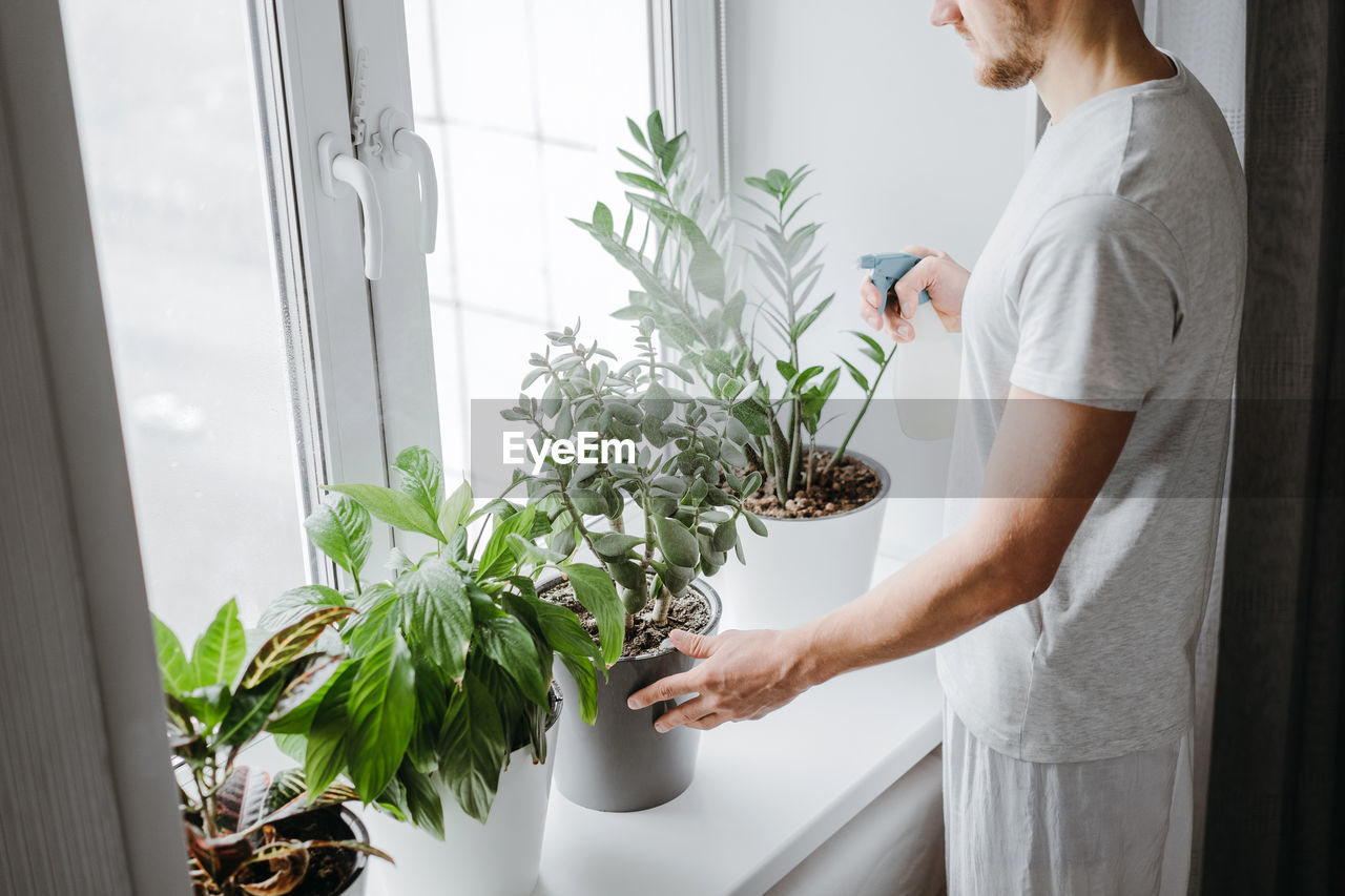 Midsection of man watering potted plants at home