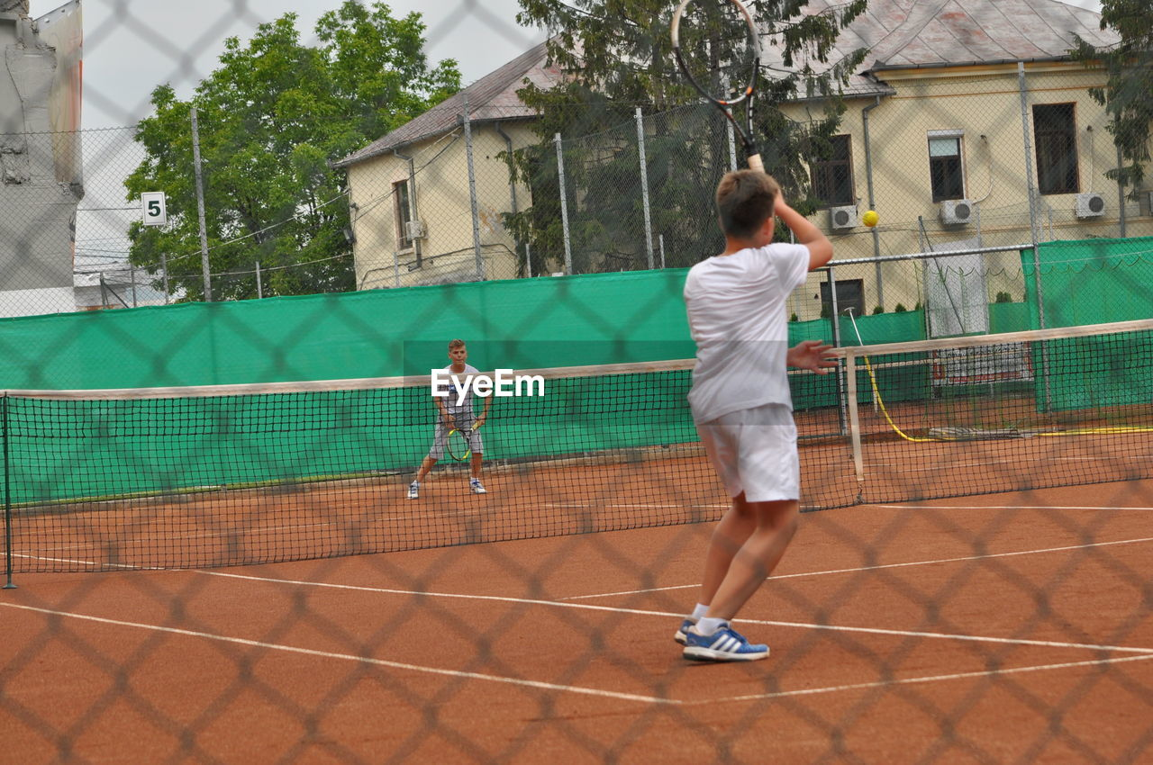 sport, tennis, court, full length, playing, tennis racket, real people, rear view, leisure activity, tennis ball, built structure, lifestyles, outdoors, day, standing, practicing, tree, architecture, sports clothing, one person, young adult, adult, people