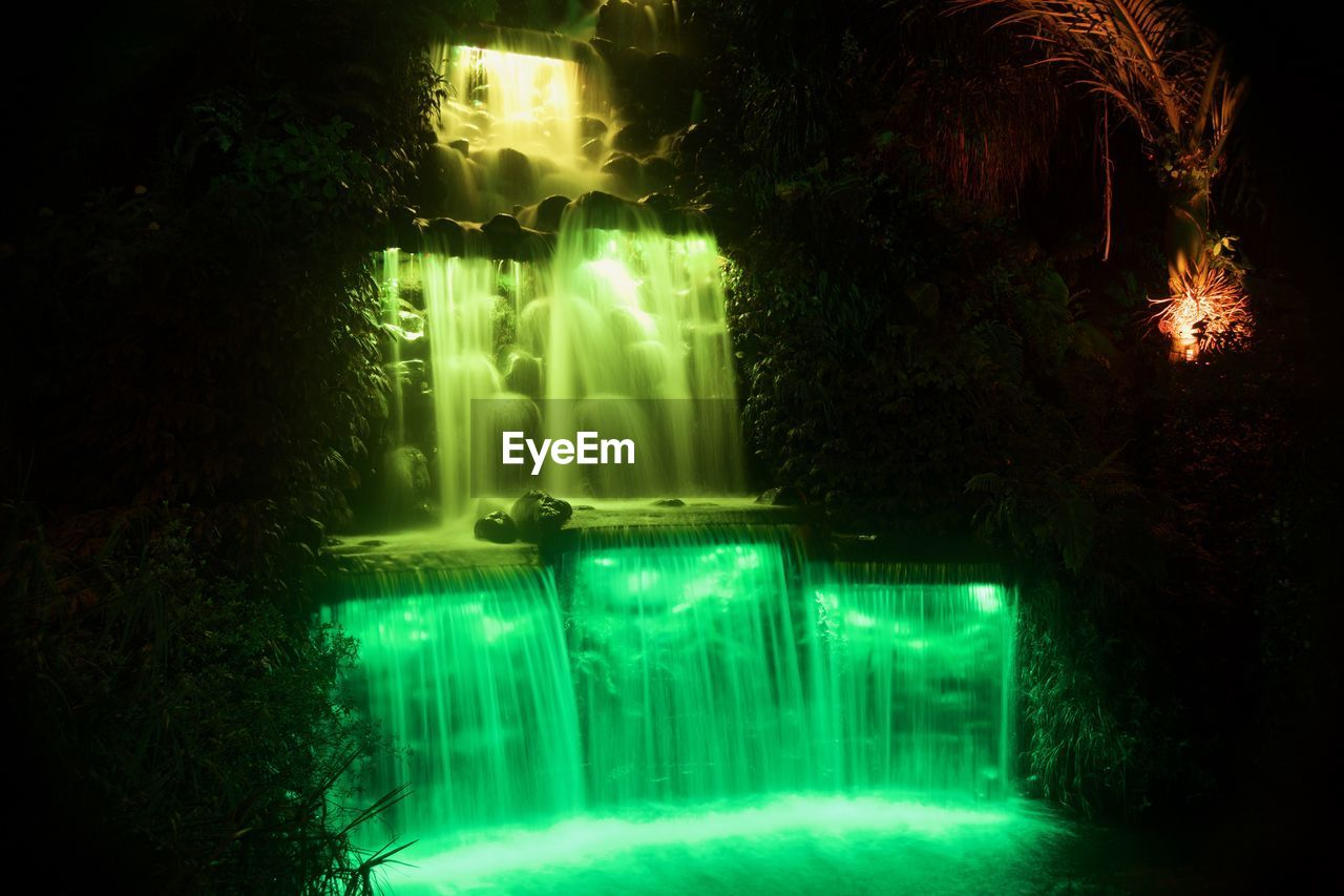 night, illuminated, water, green color, waterfall, long exposure, no people, motion, outdoors, beauty in nature, nature, growth, tree