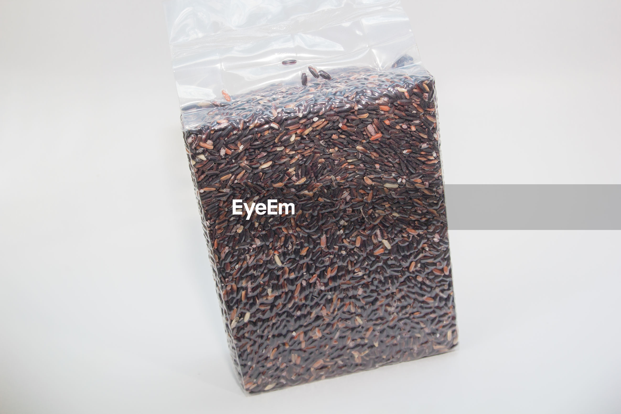 Close-up of black rice in plastic bag against gray background