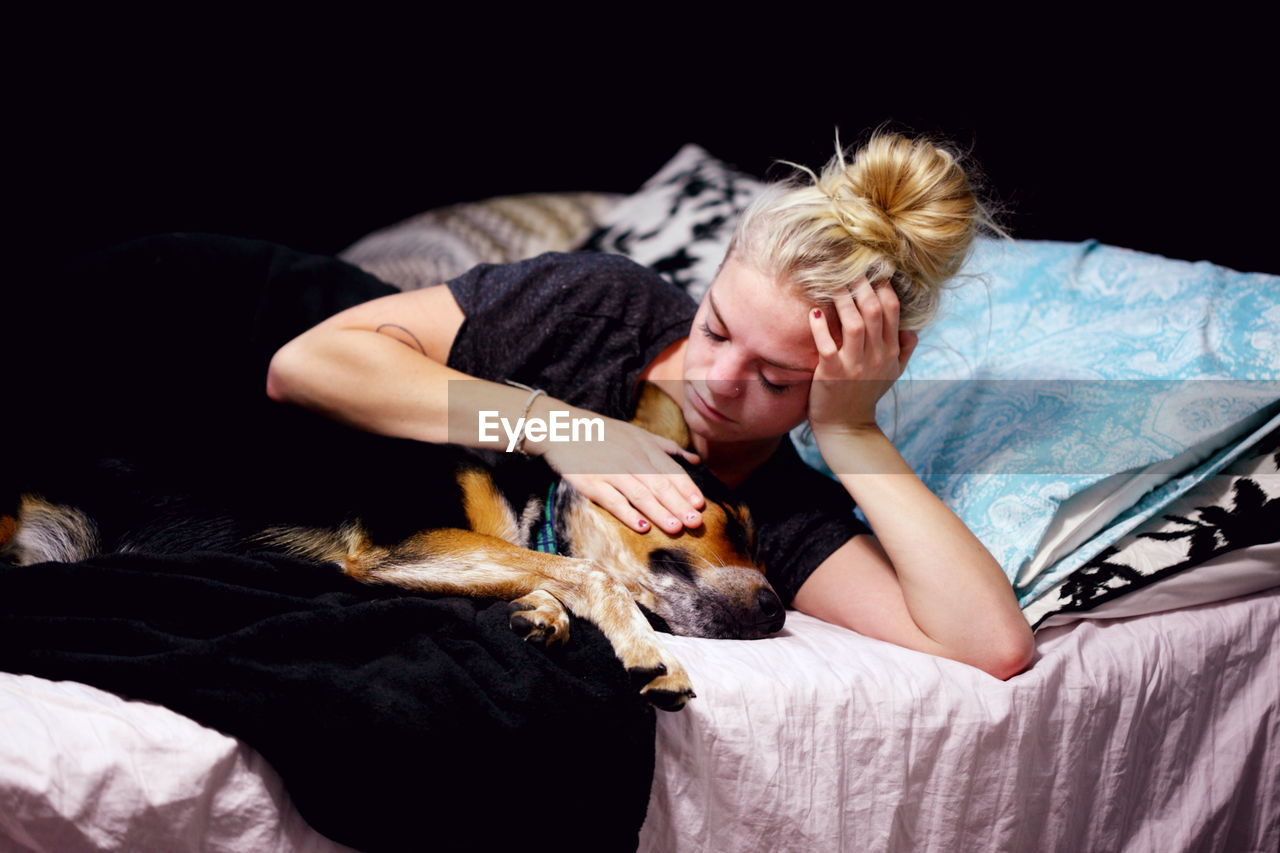 Woman petting pembroke welsh corgi while lying on bed in bedroom