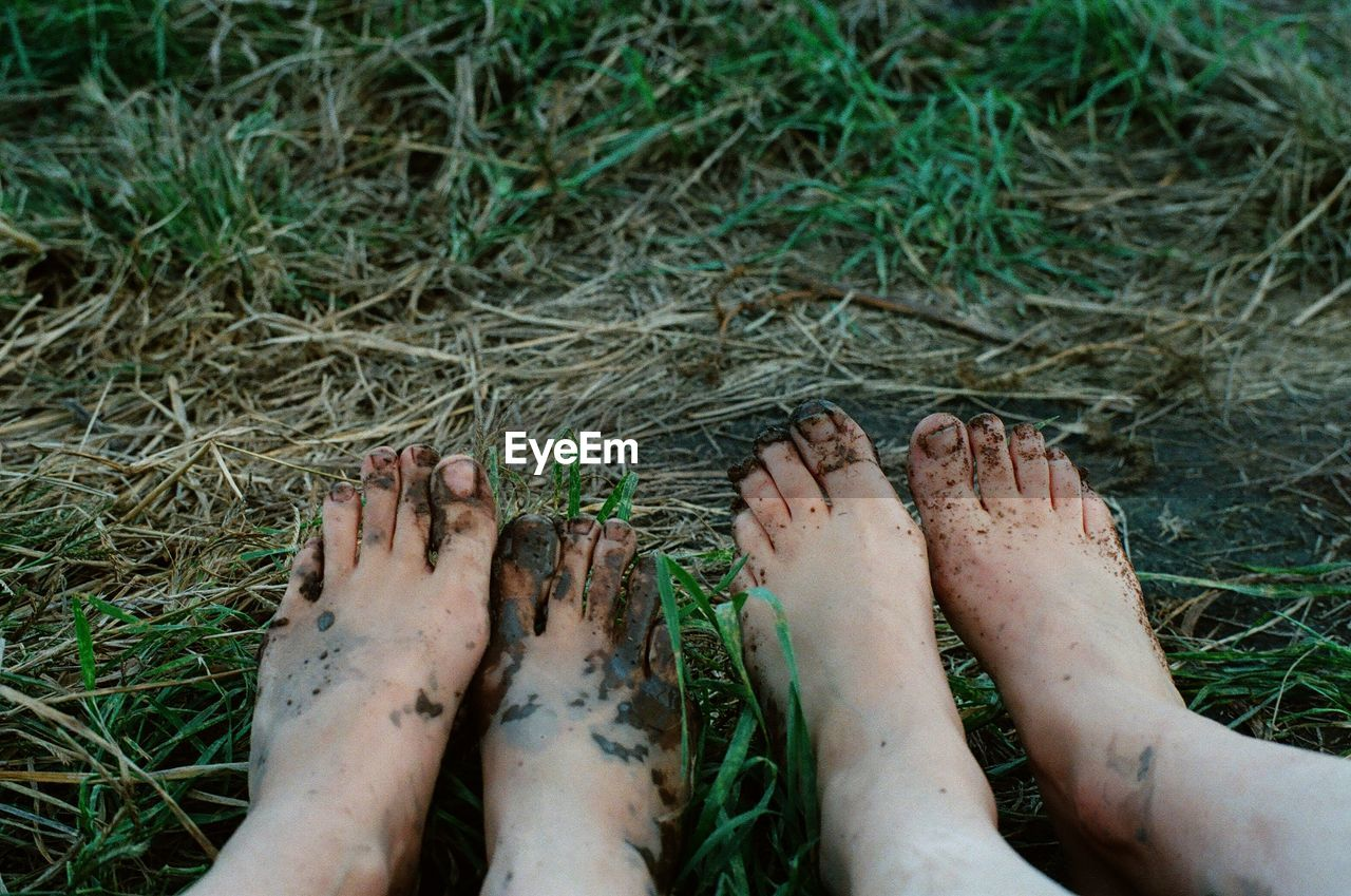 Dirty Feet Of Two Women On Grass