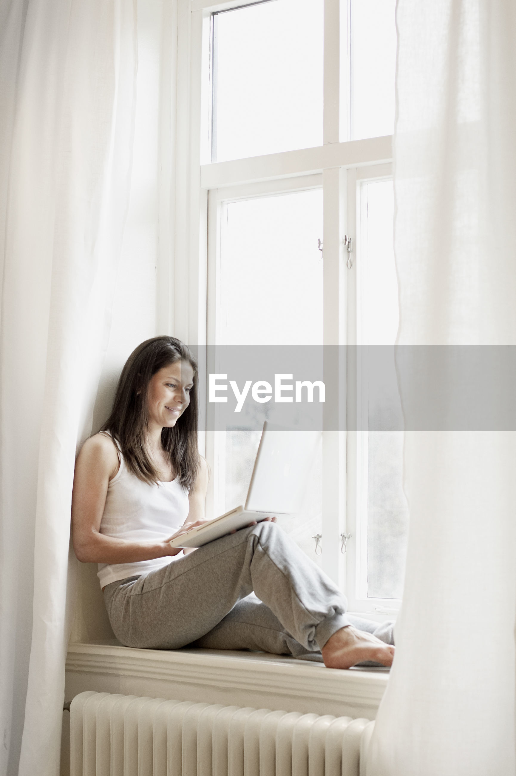 YOUNG WOMAN SITTING ON WINDOW IN HOME